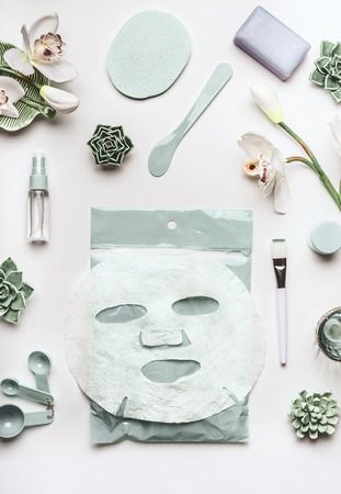 Skin care cosmetic setting with facial sheet mask , cleansing products , succulents and orchid flowers on white desktop background, top view. Beauty spa and wellness concept Stock fotó