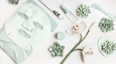 Skin care flat lay with facial sheet mask, mist spray bottle , succulents and orchid flowers on white desktop background, top view. Beauty spa and wellness concept Foto de archivo