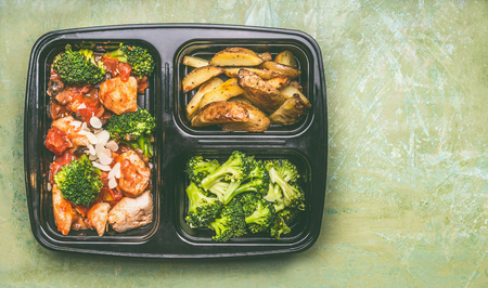 Healthy balanced lunch box with chicken pieces in tomatoes sauce with green broccoli and  baked potatoes, top view