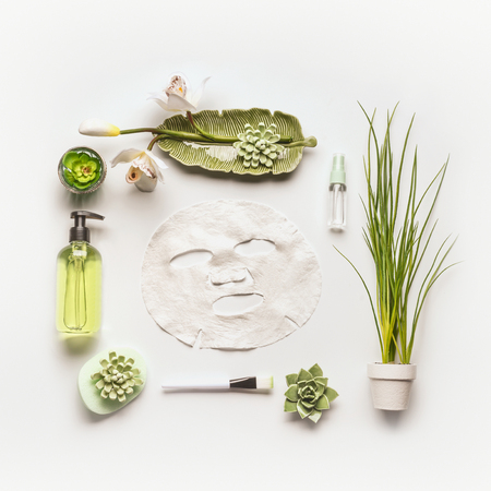 Modern facial skin care setting . Herbal cosmetic concept.  Flat lay Sheet mask with green cosmetic products, accessories, plants and orchid flowers on white desktop background, top view, copy space Stockfoto