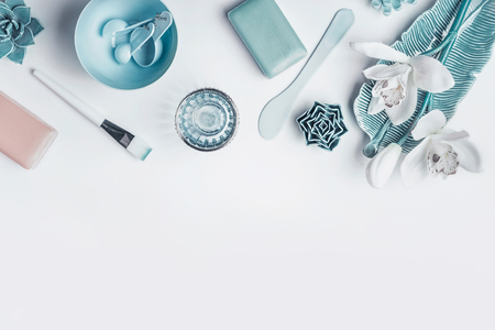 Blue Cosmetic setting for facial skin care with white orchid flowers, homemade mask tools and accessories on white background, top view, place for text. Beauty and nature herbal cosmetic concept Stock fotó