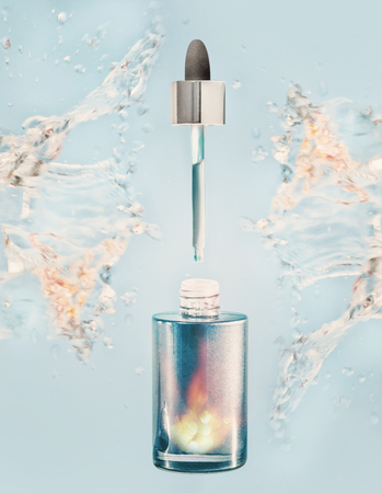 Hydrating facial serum or oil bottle with pipette and water splash on blue background, front view
