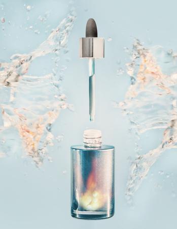 Hydratisierungsgesichtsserum oder Ölflasche mit Pipette und Wasser spritzen auf blauem Hintergrund, Vorderansicht Standard-Bild - 99227296