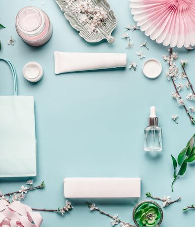 パステルブルーのデスクトップ背景に、顔の化粧品、ショッピングバッグ、小枝と桜の美しさの背景。春のスキンケアのトレンド、トップビュー、 写真素材