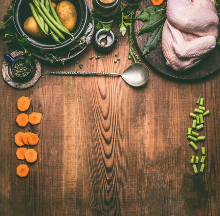 Raw whole chicken on rustic wooden kitchen table background with vegetables ingredients and spoon, top view, frame. Chicken cooking preparation