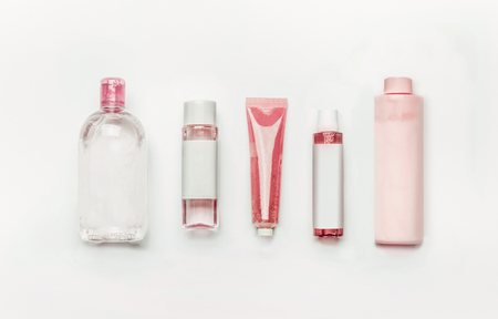 Pink natural cosmetic products : gel, lotion, serum, micellar water and toner,   bottles and tubes with branding mock up on white desk background , top view, flat lay . Facial skin care and beauty