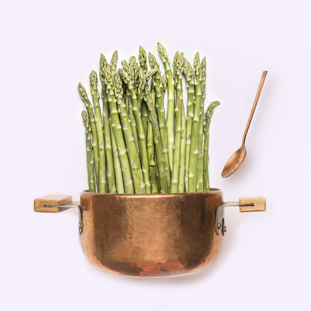 Asparagus in cooking pot with spoon on white background , front view.   Healthy vegetarian food and eating concept