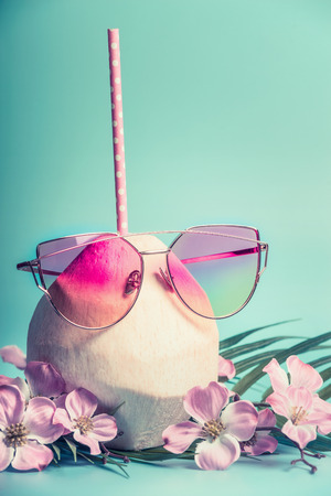 Fresh coconut cocktail  with pink drink straw, sun glasses palm leaves and tropical flowers at blue turquoise background, front view. Tropical vacation travel concept Stock Photo
