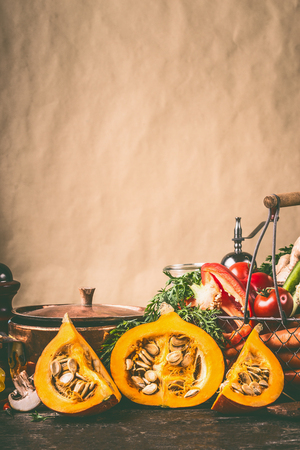 Pumpkin halves on kitchen table with cooking pot and ingredients at rustic wall background, front view. Healthy vegetarian  food and eating concept.  Autumn seasonal eating