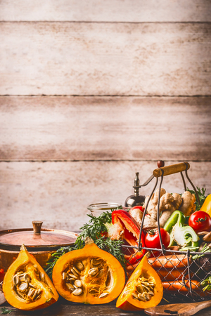 Pumpkin on kitchen table with cooking pot and ingredients at rustic wall background, front view. Healthy vegetarian  food and eating concept.  Autumn seasonal eating Stock Photo
