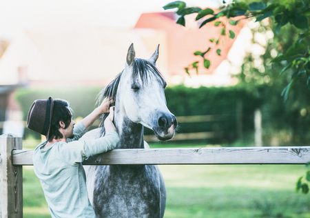 Young guy scratches his horse at summer outdoor nature