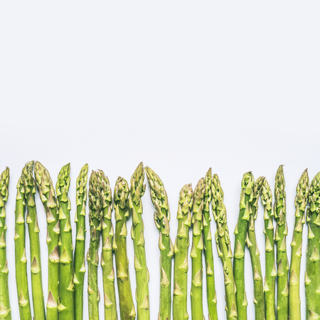 Green asparagus on white background, top view, border , place for text. Healthy seasonal food