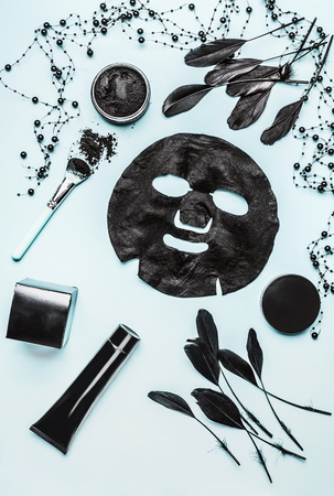Various cosmetic products with activated charcoal for facial skin care on light background, top view, flat lay. Beauty concept.  Branding mock up
