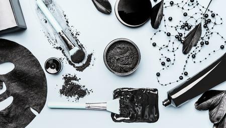Ajuste cosmético facial de carbón activado con polvo, máscara de cabeza negra, máscara de hoja y accesorios de herramientas de belleza, vista superior, endecha plana. Concepto moderno de belleza y cuidado de la piel.