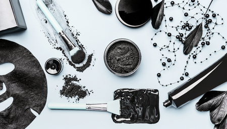 Activated Charcoal facial cosmetic setting with  powder, Black head Mask, sheet mask and beauty tools accessories , top view, flat lay. Modern beauty and skin care concept