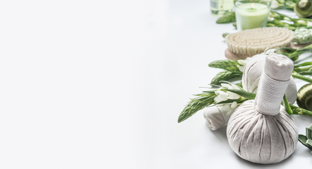 Spa background with massage herbal balls , green herbs and flowers on white. Beauty, healthy body care and wellness concept