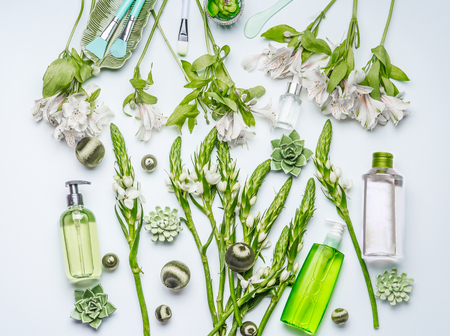 Green herbal natural cosmetic setting with bottles of facial toner, hydrophobic oil, cleansing foam, herbs and flowers on white background , top view, flat lay. Beauty and skin care concept Standard-Bild