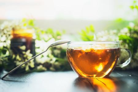 Kopje verse kruidenthee met honing op houten tafel met groene takken en bloesem, vooraanzicht. Selectieve aandacht, horizontaal. Stockfoto