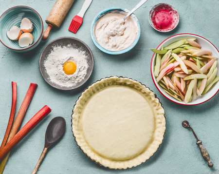 Rhubarb pie preparation. Tart baking pan with dough on kitchen table background with rolling pin, flour, egg and fresh red rhubarb stalks, top view. Seasonal cooking and baking concept