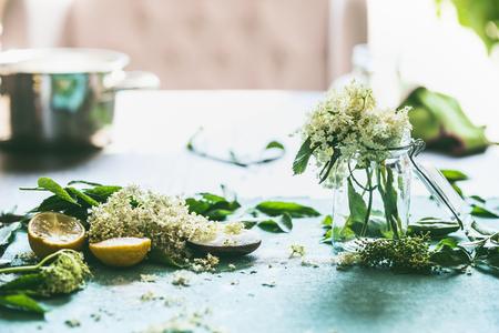 Elder flower syrup or jam preparation. Elderflowers and lemon on kitchen table at window. Home lifestyle. Healthy seasonal food eating and cooking Stok Fotoğraf