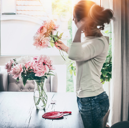 Shapely women arranging peonies bunch in glass vase on table at window with sunset light in living room. Lifestyle. Happy home