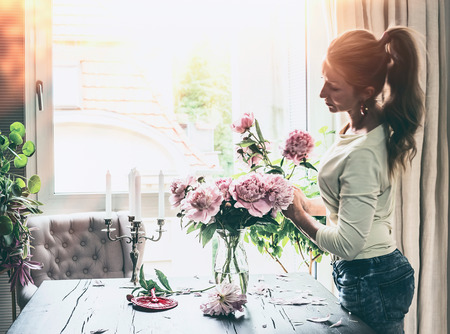 Beautiful modern women with pony tail hair arranging peonies bunch in glass vase on table at window in living room. Lifestyle. Happy home