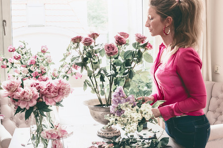 Pretty modern florist women arranging great festive flowers bouquet with urn vase, roses and various flowers at window  Step by step. Holidays and event decor ideas. Still Life. Stock Photo