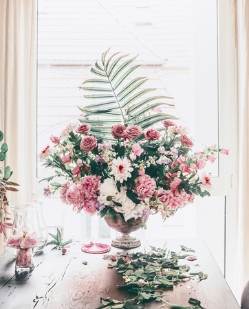 Event flowers arrangement. Great festive classical bouquet with various flowers and palm leaves in urn vase on table at window in living room. Holidays decor ideas. Still Life. Home interior