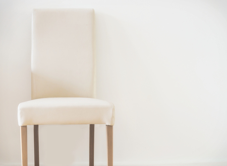 White leather stool and copy space on the wall. Simple interior