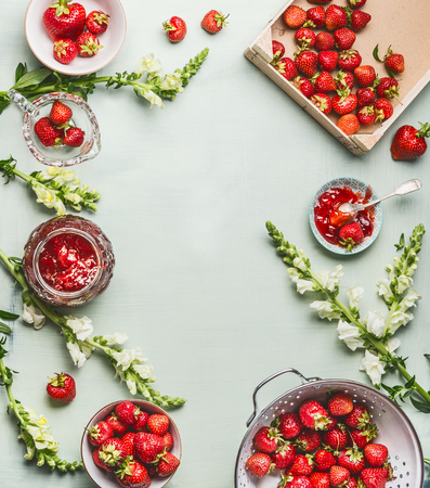 Strawberries homemade jam in glass jar with summer flowers and fresh berries on table background, top view. Berries preserve concept, frame Stock Photo