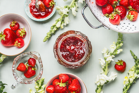 Strawberries homemade jam in glass jar with summer flowers and fresh berries on table background, top view. Berries preserve concept Stockfoto - 104634421