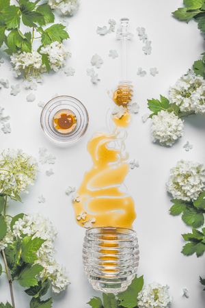 Honey pours from a glass jar on white table background with wild flowers and blossom, top view. Concept of healthy food and organic nutrition