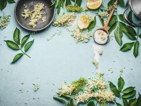 Oudere bloemen koken voorbereiding. Oudere bloemen met lepel, suiker en citroen op blauwe tafelachtergrond, bovenaanzicht