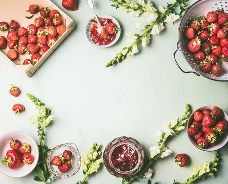 Frame made with fresh strawberries in colander and bowls with jam jar and spoon on kitchen table background with garden flowers, top view. Summer berries preserve concept. Seasonal local organic food