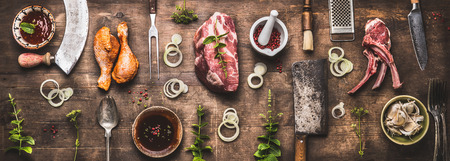 Flat lay of various grill and bbq meat : chicken legs, steaks, lamb ribs with vintage kitchenware kitchen utensils:  Meat Fork and Butcher Cleaver and herbs knife. Sauces and ingredients for grilling, Archivio Fotografico