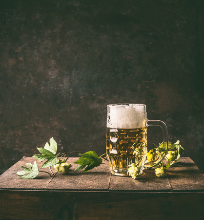 Cold mug of beer with foam on a rustic table with a vine and cones of hops opposite a dark wall, front view.