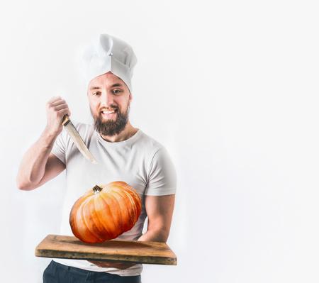 Junger glücklicher Mann mit Bart hält einen Kürbis und ein Messer. Erntedankfest Kochen oder Herbst Rezepte Konzept