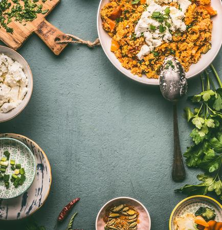 Lebensmittelhintergrundrahmen mit gesundem vegetarischem Couscous-Topf und Schalen mit Zutaten: Gemüse, Kräuter und Feta-Käse auf dunklem Tisch, Draufsicht, flache Lage, Rahmen