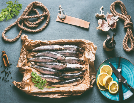 Raw sardines on kitchen table background with ingredients . lemon, garlic and herbs for tasty seafood cooking. Cooking preparation of fishes Stock Photo