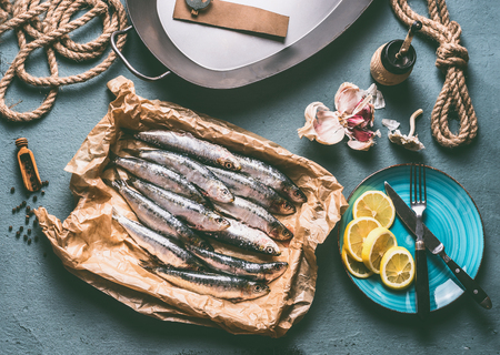 Raw sardines on kitchen table background with frying pan and ingredients for tasty seafood cooking. Cooking preparation of fishes