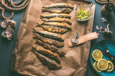 Grilled sardines on baking tray with ingredients: lemon, garlic and herbs for tasty seafood eating. Cooking preparation of fishes