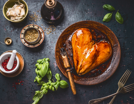Chicken breast meat in heart shape with rub brush and marinate for cooking or grill on rustic dark background with ingredients bowls: herbs, spices and sauce, top view . Protein fitness food 版權商用圖片