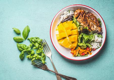 Sabrosa ensalada de verano con pollo asado y mango en un tazón con cubiertos sobre fondo azul claro, vista superior. Almuerzo saludable bajo en carbohidratos