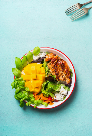 Tasty salad with roasted sliced chicken breast and mango in bowl with cutlery on light blue background, top view. Healthy lunch Stock Photo