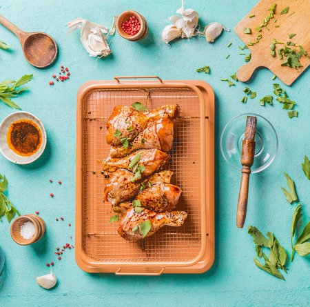 Cooking preparation of raw chicken drumsticks. Raw marinated Chicken legs on grill grid with ingredients,  herbs, spices , sauce and cooking spoon on light blue kitchen table background, top view Zdjęcie Seryjne
