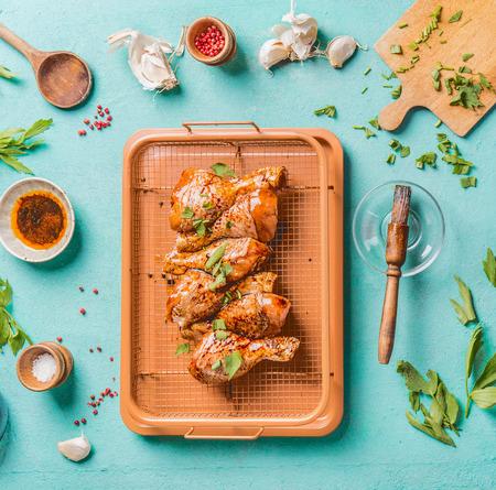 Preparazione della cottura delle cosce di pollo crude. Cosce di pollo marinate crude sulla griglia della griglia con gli ingredienti, le erbe, le spezie, la salsa ed il cucchiaio da cucina sul fondo blu-chiaro del tavolo da cucina, vista superiore