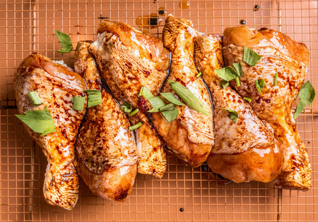 Close up of Raw marinated chicken drumsticks on grill grid with ingredients, herbs and spices, top view