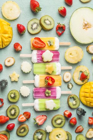 Colorful variety of ice  with fresh sliced fruits and berries ingredients on blue background, top view, flat lay. Frozen tropical juices. Homemade ice cream lined up in a row