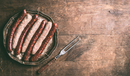 Beef and pork sausages for grill or bbq on dark vintage plate with meet fork on rustic wooden background, top view. Place for your design, text or recipes Stock Photo