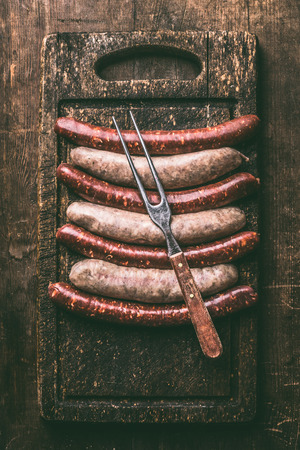 Pork sausages for grill or bbq on dark vintage cutting board with meet fork and napkin on rustic wooden background, top view. Place for your design, text or recipes